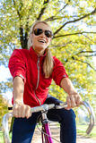 Femme heureux faisant un cycle sur la bicyclette en stationnement photographie stock libre de droits