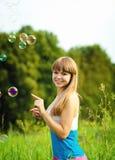 Femme heureux jouant avec des bulles de savon Photo stock