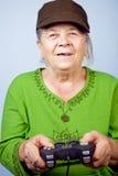 Femme aîné heureux jouant des jeux vidéo Images stock