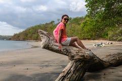 Femme heureux s'asseyant sur un tronçon Image libre de droits