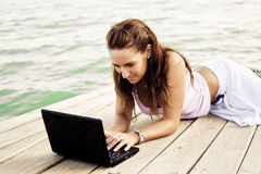 Femme heureux sur l'ordinateur portatif Images libres de droits