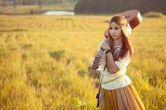 Femme hippie marchant dans le domaine d'or Photo stock