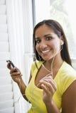 Femme hispanique écoutant la musique sur le joueur mp3 photographie stock