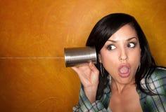 Femme hispanique avec le téléphone de boîte en fer blanc Images stock