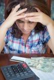 Femme hispanique comptant l'argent à la maison pour payer les factures Photo stock
