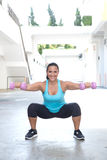 Femme hispanique de sport faisant des postures accroupies avec l'haltère deux rose, extérieure Photographie stock