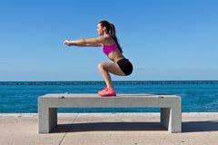 Femme hispanique faisant des postures accroupies par l'eau photographie stock libre de droits