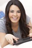 Femme hispanique heureuse utilisant l'ordinateur ou l'iPad de tablette Photos libres de droits