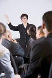 Femme hispanique parlant au groupe d'hommes d'affaires Images stock