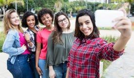 Femme hispanique prenant le selfie avec le groupe de girlfri international Image stock