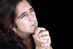 Femme hispanique priant et embrassant un crucifix Photographie stock libre de droits