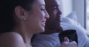Femme hispanique riant et souriant tout en buvant du café avec l'ami noir dans le lit Image stock