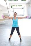 Femme hispanique sportive dans le bleu soulevant l'haltère rose étirant les deux bras pour le bâtiment de biceps, dehors Images stock