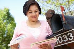 Femme hispanique supérieure vérifiant la boîte aux lettres images libres de droits
