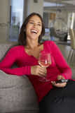 Femme hispanique sur le vin potable de Sofa Watching TV Images libres de droits