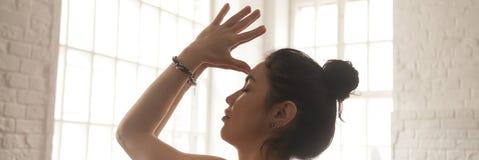 Femme horizontale de photo faisant des mains de contact de geste de namaste au front photo stock