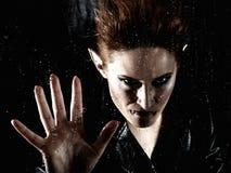 Femme horrible de vampire derrière l'hublot pluvieux photo stock