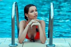 Femme humide rêvant sur le bord de la piscine Image stock