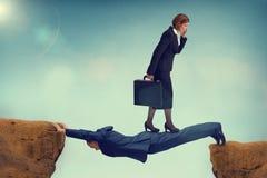 Femme impitoyable d'affaires marchant au-dessus d'un homme d'affaires vulnérable Image stock