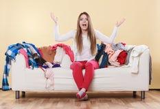 Femme impuissante s'asseyant sur le sofa dans la maison malpropre de chambre photos stock