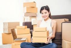 Femme indépendante tenant des boîtes fonctionnant à la maison le concept photo libre de droits