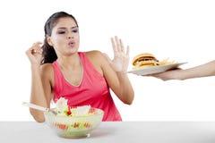 Femme indienne rejetant l'hamburger sur le studio images stock