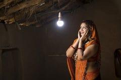 Femme indienne rurale ravie sur l'électricité atteignant sa maison image libre de droits