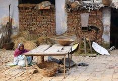 Femme indienne s'asseyant devant sa maison Images stock