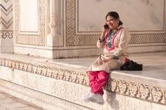 Femme indienne traditionnellement habillée causant heureusement le matin lumineux le Taj Mahal photo stock