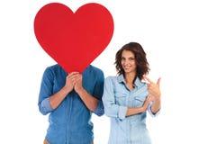 Femme indiquant le doigt son amant tenant le coeur au-dessus du visage Photographie stock libre de droits