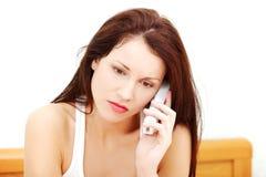 Femme inquiété parlant au téléphone. Image stock