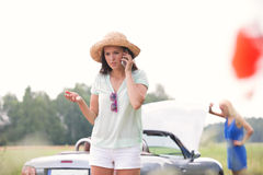 Femme inquiétée à l'aide du téléphone portable tandis qu'ami examinant la voiture décomposée dehors Photographie stock