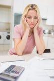 Femme inquiétée avec des factures et calculatrice dans la cuisine Photos libres de droits