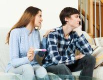 Femme inquiétée avec l'essai de grossesse avec l'homme malheureux Images stock