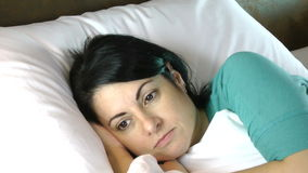 Femme inquiétée dans le lit banque de vidéos