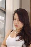 Femme inquiétée et triste regardant à l'extérieur l'hublot Photo stock