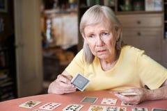 Femme inquiétée jouant des cartes à la table Photographie stock libre de droits