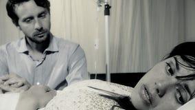 Femme inquiétée malade malade dans le lit d'hôpital avec son mari Images libres de droits
