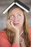 Femme inquiétée réfléchie avec le livre sur la tête Image stock