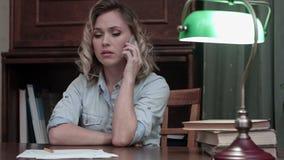 Femme inquiétée répondant à un appel téléphonique avec la mauvaise nouvelle et prenant sa tête dans des mains banque de vidéos