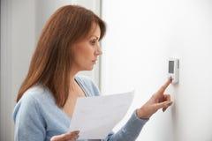 Femme inquiétée tournant vers le bas le thermostat de chauffage central photographie stock