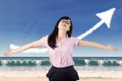 Femme insouciante célébrant son succès à la plage Photographie stock libre de droits
