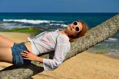 Femme insouciante détendant sur la plage tropicale Photographie stock libre de droits