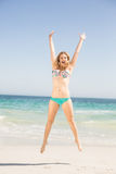 Femme insouciante dans le bikini sautant sur la plage Photographie stock