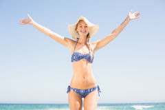 Femme insouciante dans le bikini se tenant sur la plage images stock