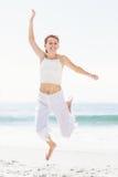 Femme insouciante en sautant sur la plage photos stock