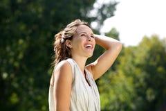Femme insouciante souriant avec la main dans les cheveux dehors Photos libres de droits