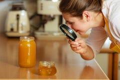 Femme inspectant le miel avec la loupe Photos stock