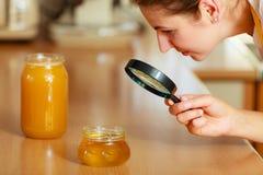 Femme inspectant le miel avec la loupe photographie stock