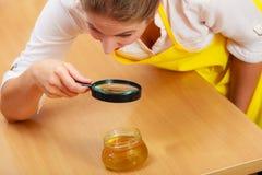 Femme inspectant le miel avec la loupe photographie stock libre de droits